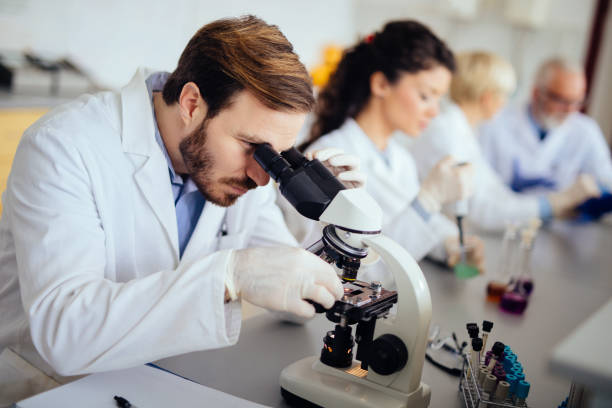Young male scientist looking through a microscope stock photo