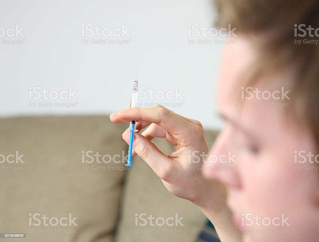 Young male self-injecting anti-coagulant to prevent blood clots after accident stock photo