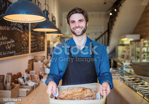 istock A young male shop assistant holding a basket with bread in a zero-waste store. 1027539414