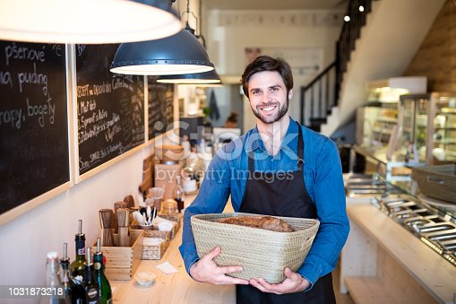 istock A young male shop assistant holding a basket with bread in a zero-waste store. 1031873218
