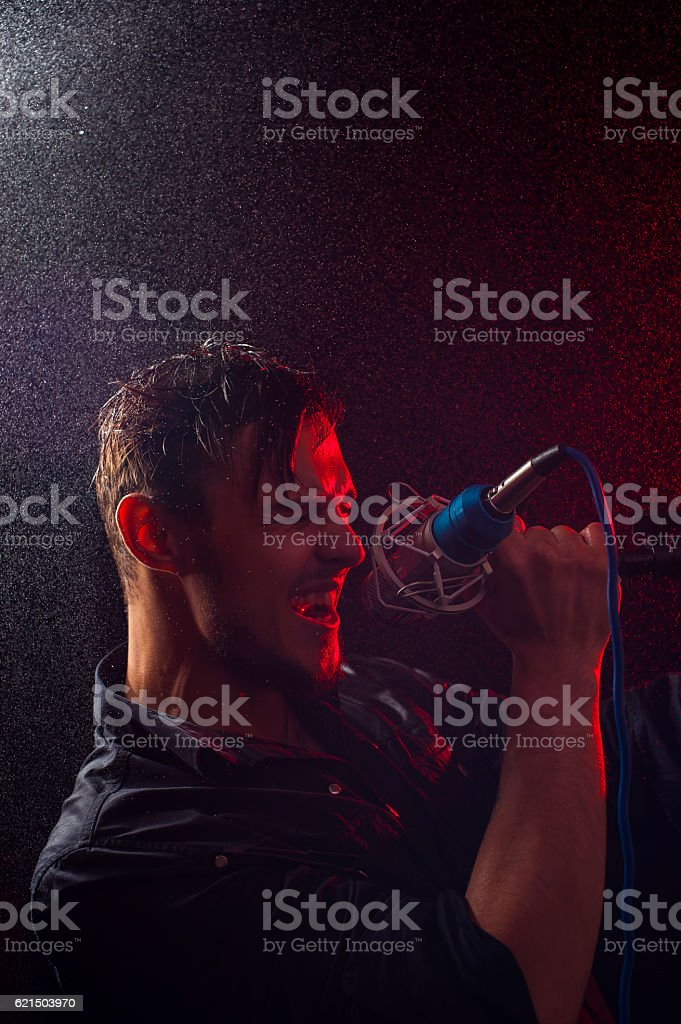 Young male singer performing with microphone photo libre de droits