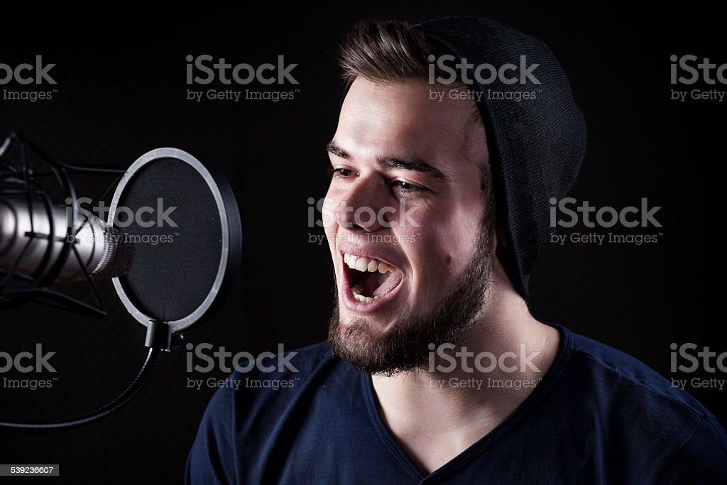 Young male singer at the sound recording studio, performing in front...