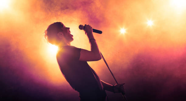 young male singer with a microphone performing on stage in backlit - rock music stock pictures, royalty-free photos & images