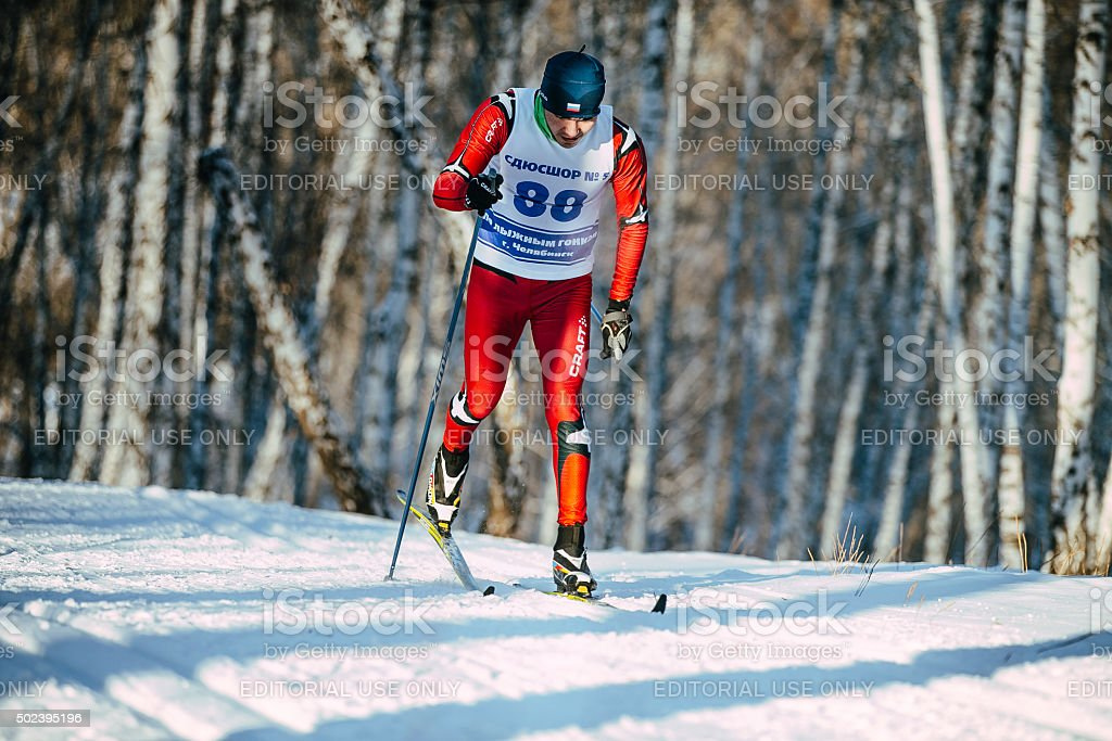 young male skier classic style in winter forest stock photo