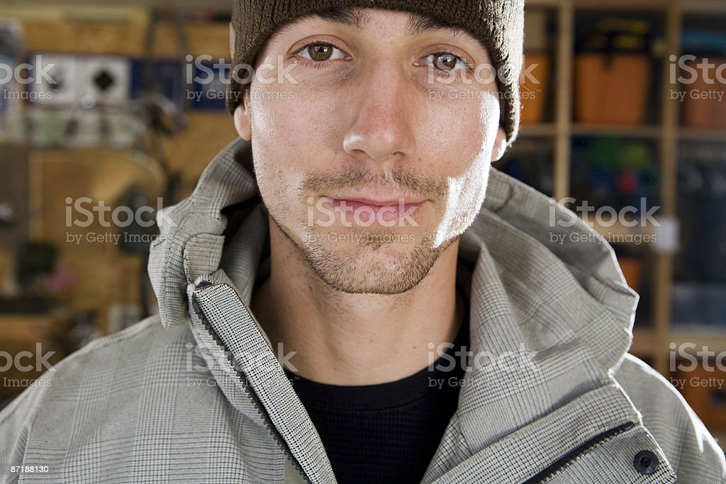 A young male skier standing in his gear room. royalty-free stock photo