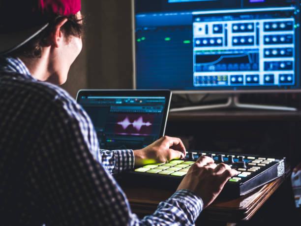 jonge mannelijke geluidstechnicus werken in professionele muziekstudio met moderne apparatuur voor het opnemen van nieuwe track - hand constructing industry stockfoto's en -beelden