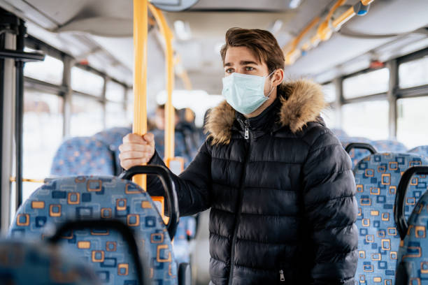 Young male standing on a bus wearing sterile face mask stock photo