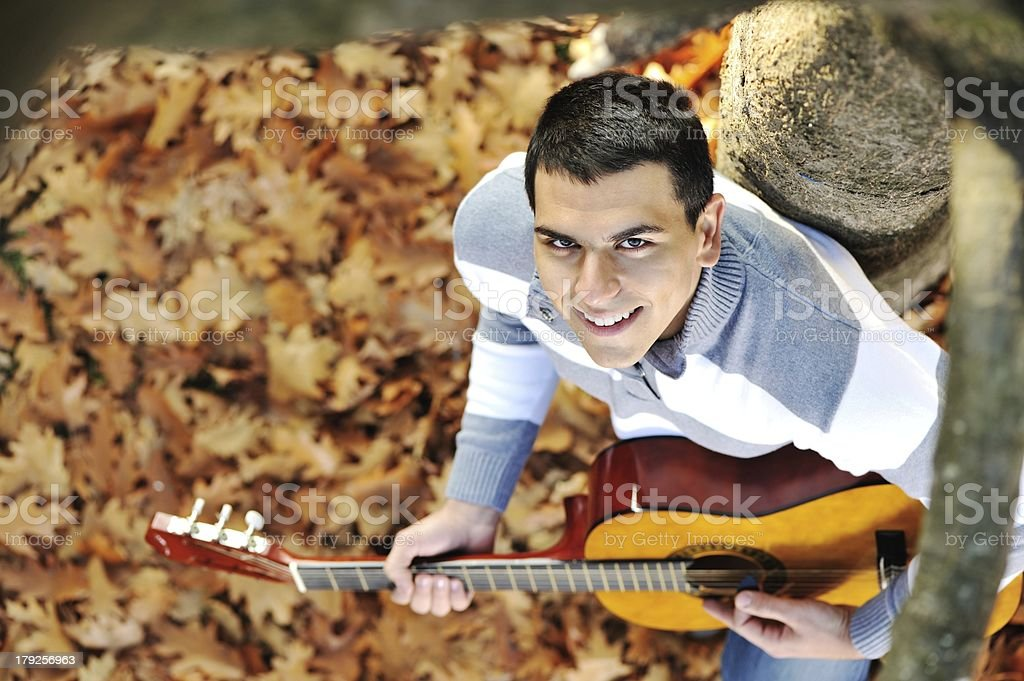 Young male standing with guitar at park royalty-free stock photo