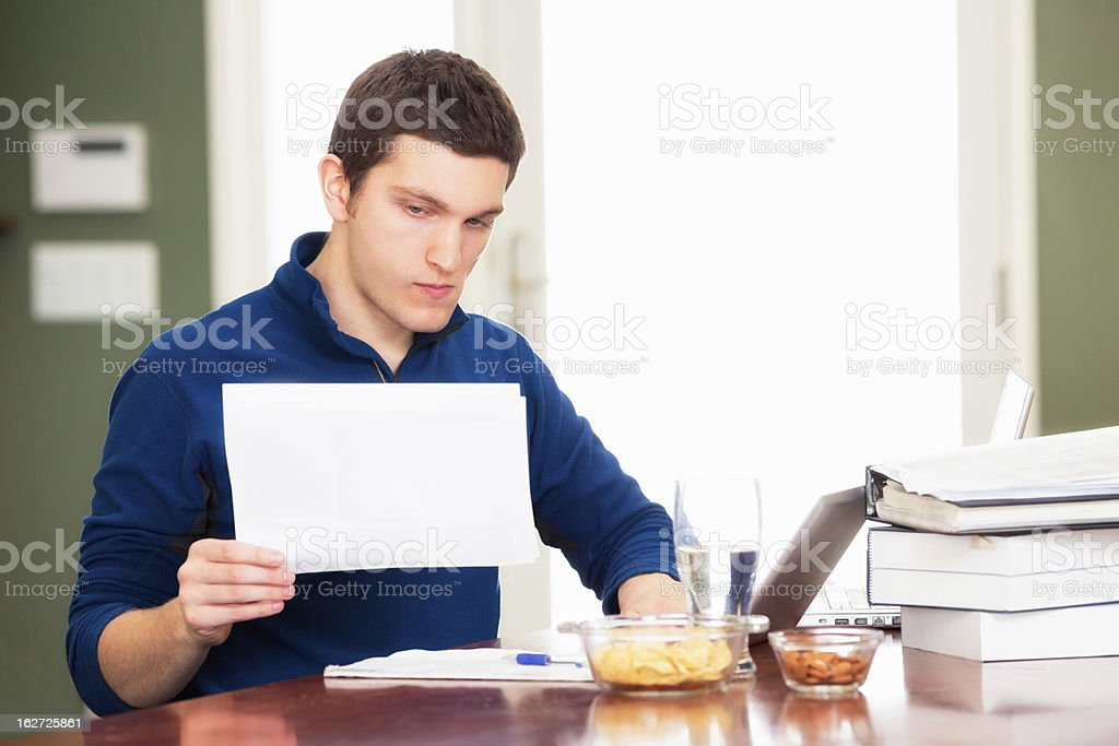 Young male student entrepreneur pondering information royalty-free stock photo