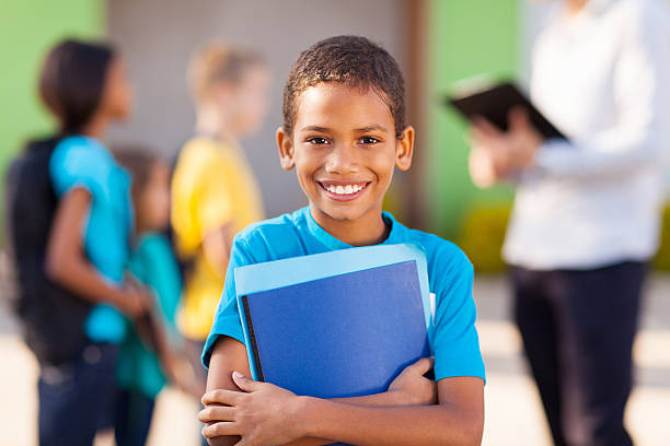 Young male student holding folders and smiling stock photo