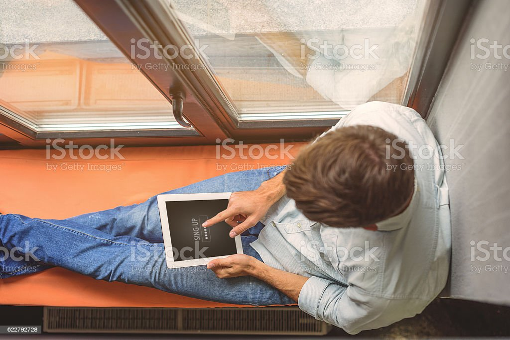 young male student learning by gadget stock photo