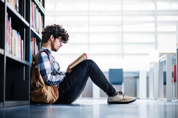 junge männliche schüler lesen ein buch in einer bibliothek. - leseunterricht stock-fotos und bilder