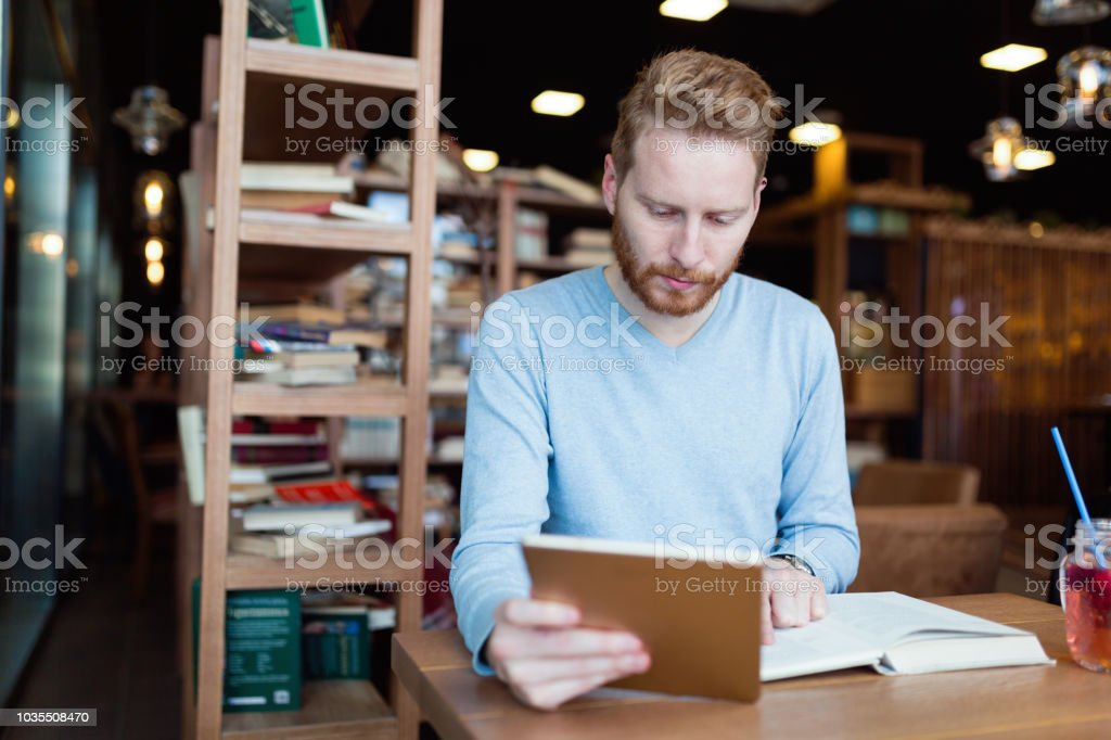 Young male student reading in coffee shop stock photo