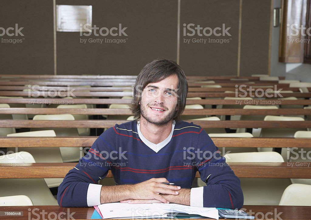 A young male student sitting in a classroom alone royalty-free stock photo