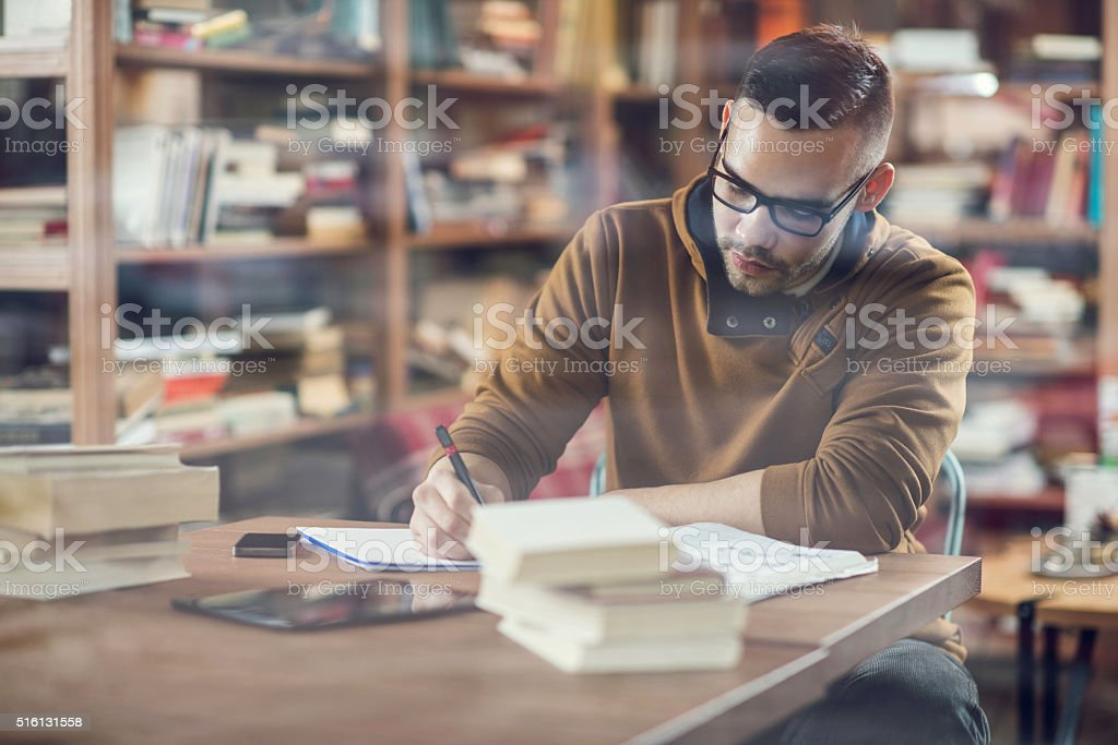 Young male student taking notes for his exams in library. stock photo