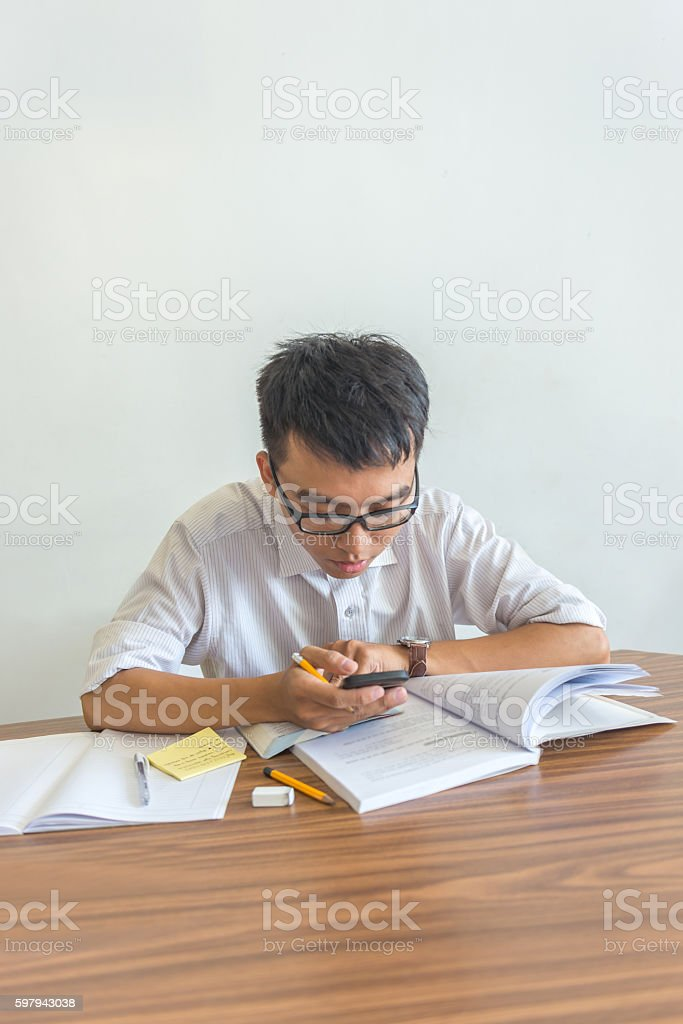 Young male student using smartphone while doing homework foto royalty-free