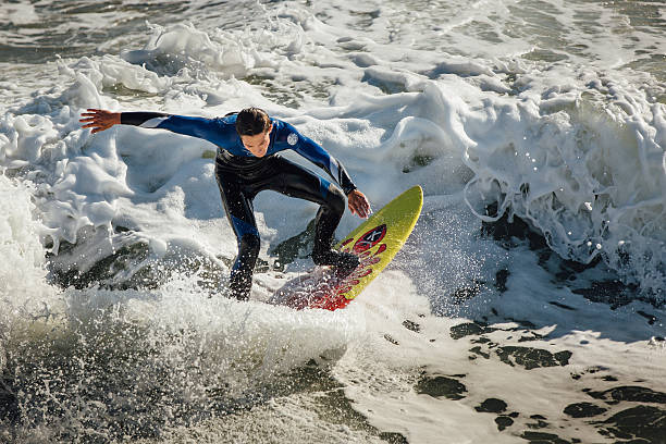 Young male surfer riding a frothy wave stock photo
