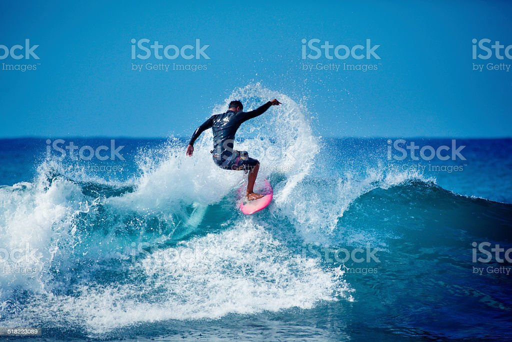 Young Male Surfer Surfing in the Water of Hawaii stock photo