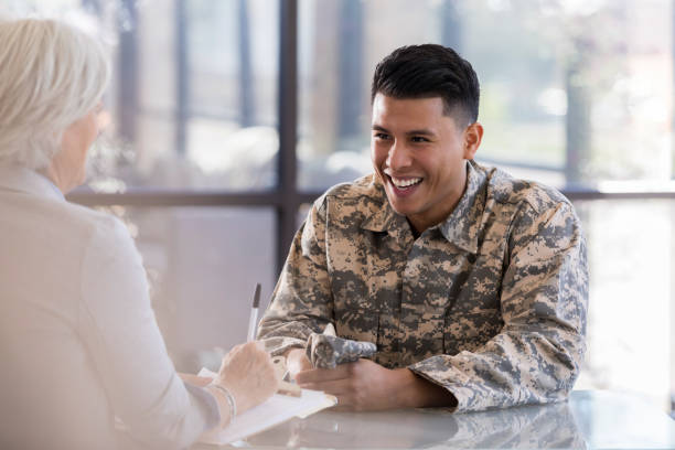 Young male talks with a female counselor and smiles Young, mid-adult male in military uniform sits at a table with mature, female counselor. He smiles at her as she takes notes on their conversation. military lifestyle stock pictures, royalty-free photos & images