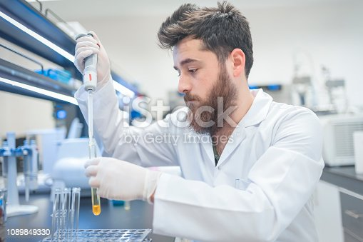 Young male tech or scientist loads sample with automatic pipette