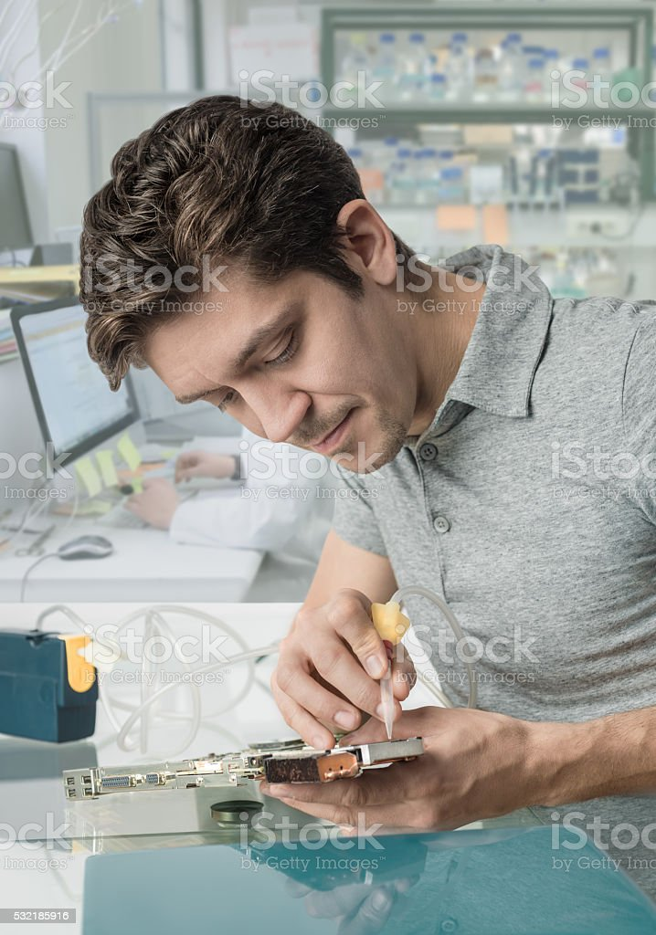 Young male tech works in in research facility stock photo