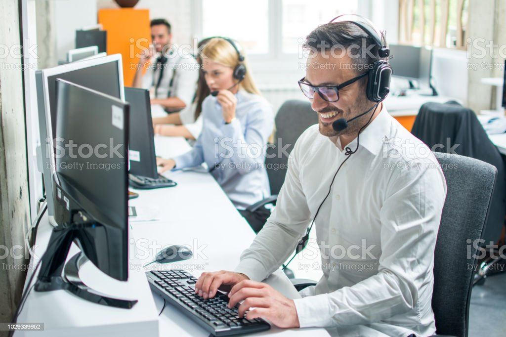 Young male technical support dispatcher with headset talking with customer in call center stock photo