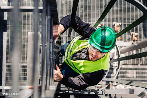 istock Young male technician climbing ladder in industry 490606938