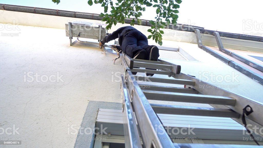 Young male technician repairing outdoor air conditioning system...