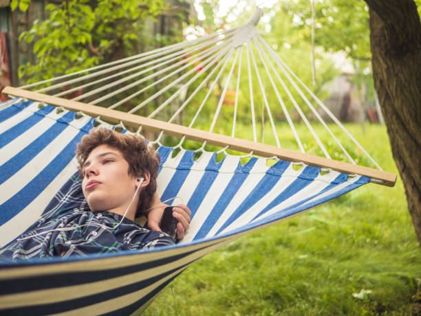 young male teenager sleeping on the hammock in garden on a summer day stock photo