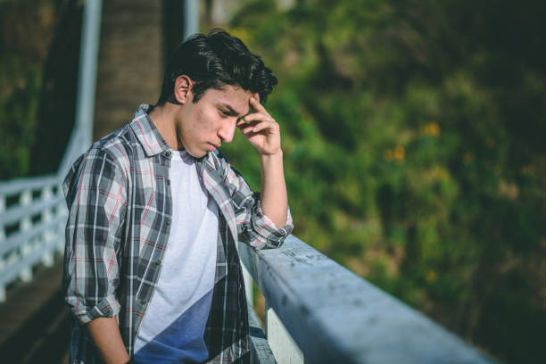 Young male teenager with depression contemplating suicide Young male teenager with depression contemplating suicide standing on a bridge male likeness stock pictures, royalty-free photos & images