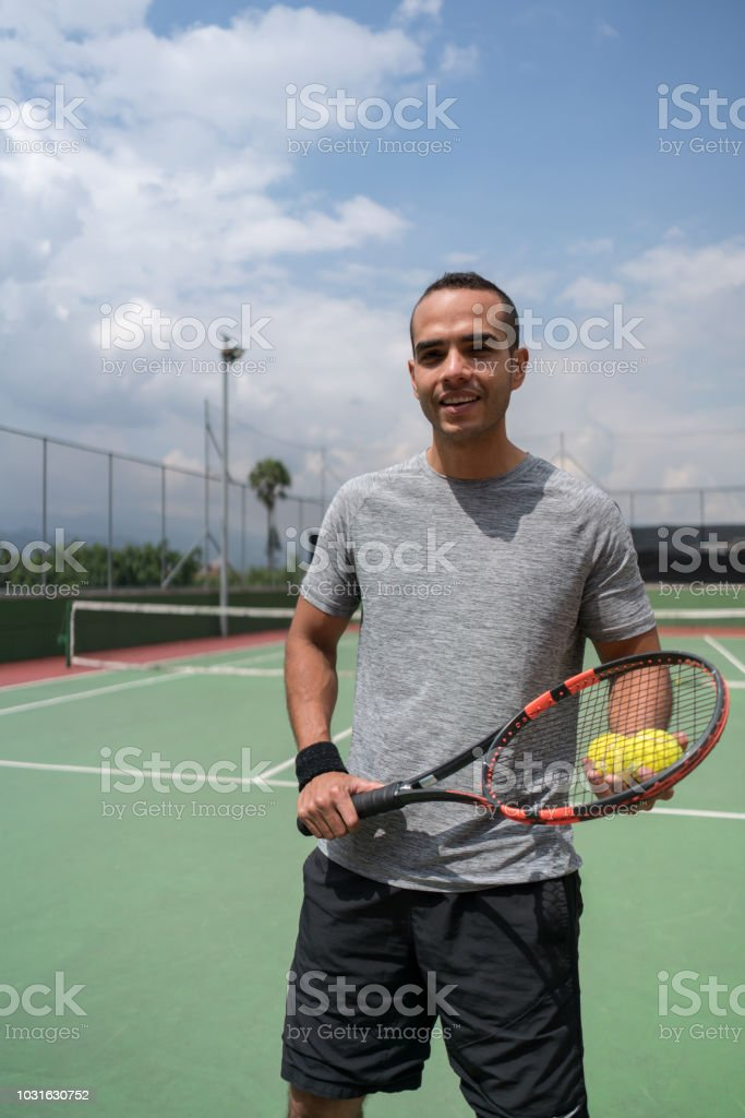 Young male tennis player holding a tennis racket and balls looking at...