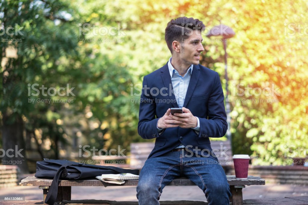Young male texting on his mobile phone royalty-free stock photo