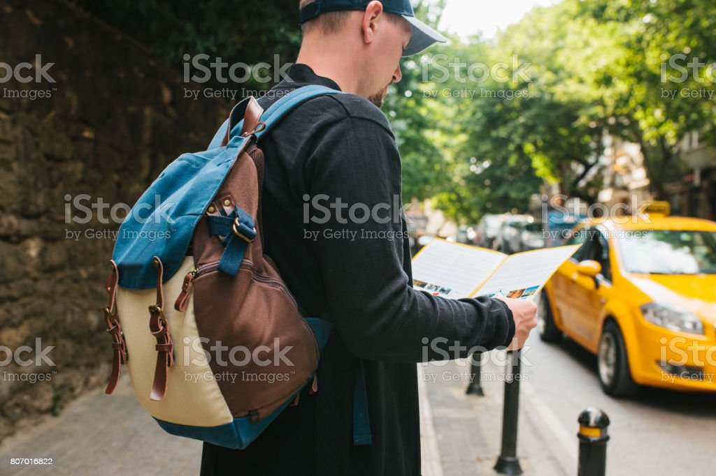 Young male tourist with a backpack in a big city is watching a map. Journey. Sightseeing. Travel. stock photo