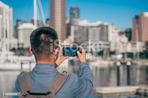 young male tourists take photo with auckland sky tower