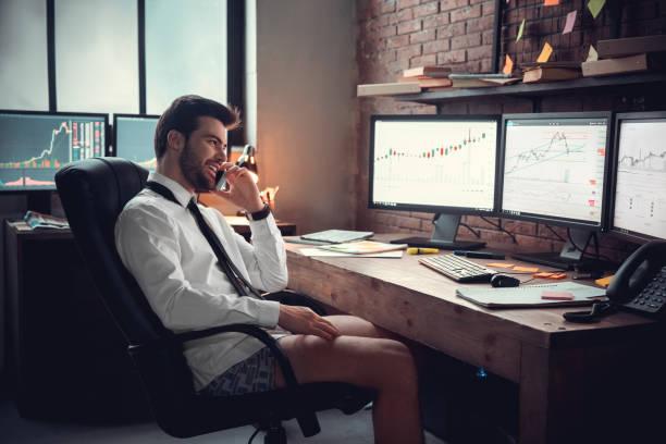 jeune commerçant mâle au concept de travail de bureau se reposant dans des sous-vêtements ayant l'appel téléphonique - homme slip photos et images de collection