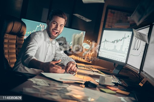 Young bearded man trader at office sitting at table looking camera smiling cheerful