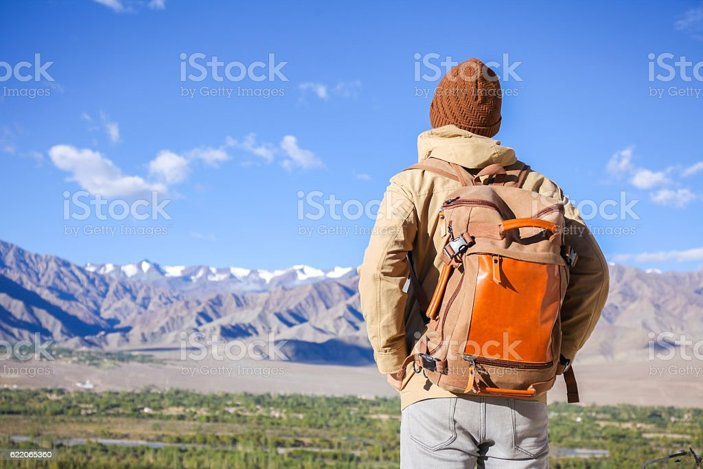 Young male travel backpacker watching mountains stock photo