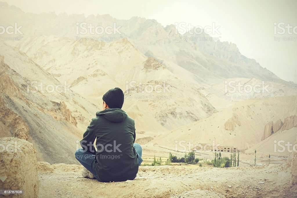 Young male traveler sitting on the sand cliff stock photo