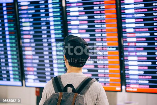 istock Young male traveler watching and waiting for flight time schedule on boarding time monitor screen 936398210