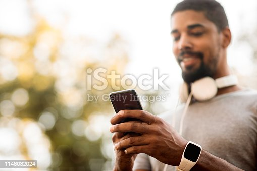 istock Young male using online chat on a mobile phone in a park 1146032024