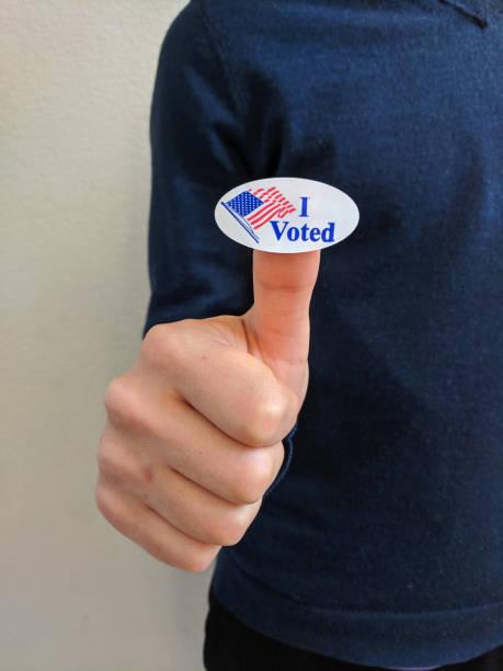 """junge männliche wähler halten einen """"ich habe gewählt"""" aufkleber auf seinem daumen - aufkleber stock-fotos und bilder"""