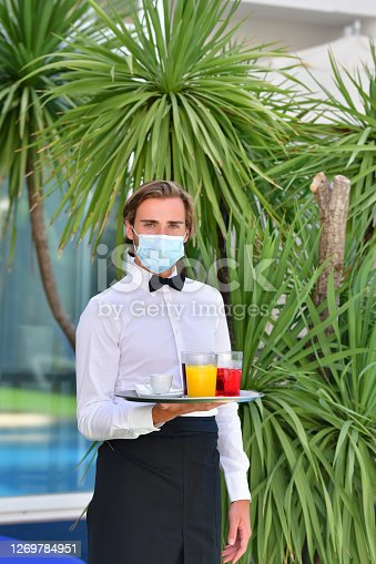 Young male waiter with a surgical mask holding a bar tray with assorted drinks outdoors on an out of focus background. Serving and safety concept.
