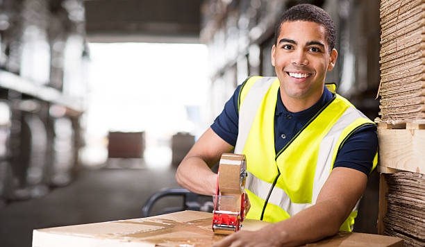 young male warehouse worker packing boxes for shipment stock photo