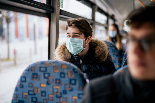 Young male wearing protective face mask while traveling with public transport stock photo