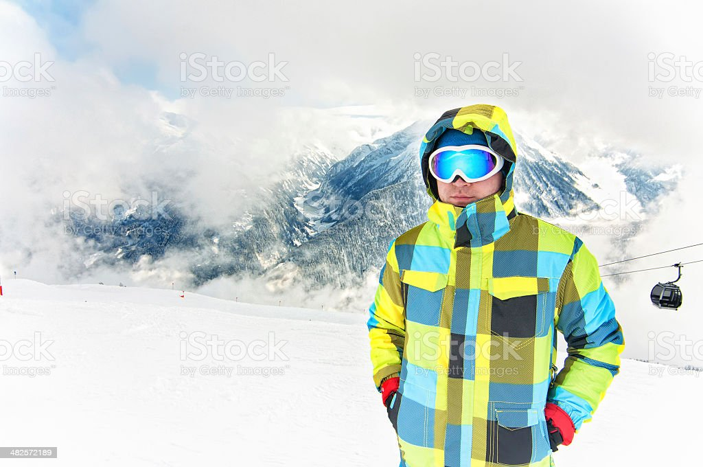 Young male wearing winter snowboarding costume on top of alpine...