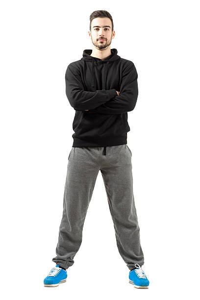 junger mann mit gekreuzten händen gefaltet oder im sportswear - trainingshose stock-fotos und bilder