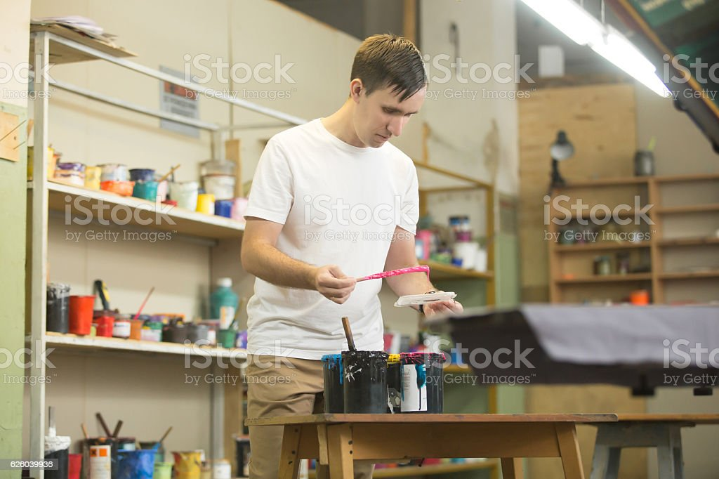 Young male worker choosing appropriate inks stock photo