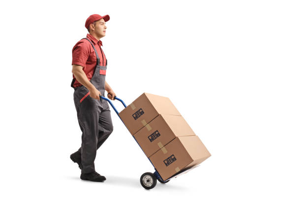 Young male worker in a uniform pushing boxes on a hand truck Full length shot of a young male worker in a uniform pushing boxes on a hand truck isolated on white background carrying stock pictures, royalty-free photos & images