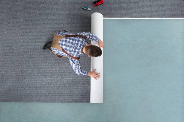 jonge mannelijke werknemer in overalls rollen tapijt - aanbrengen stockfoto's en -beelden