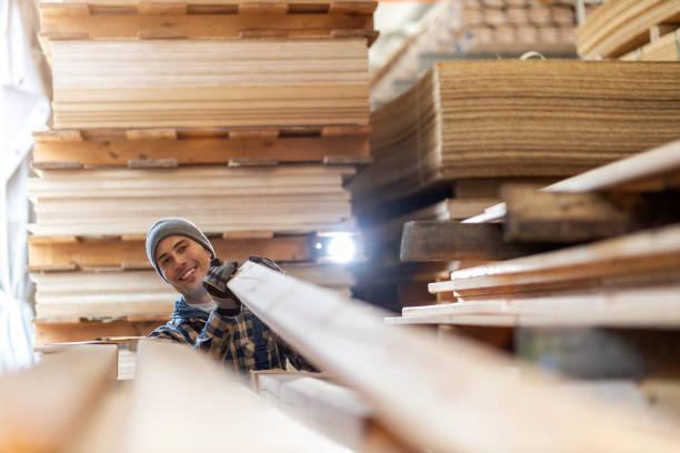 Junger männlicher Arbeiter im Holzlager – Foto